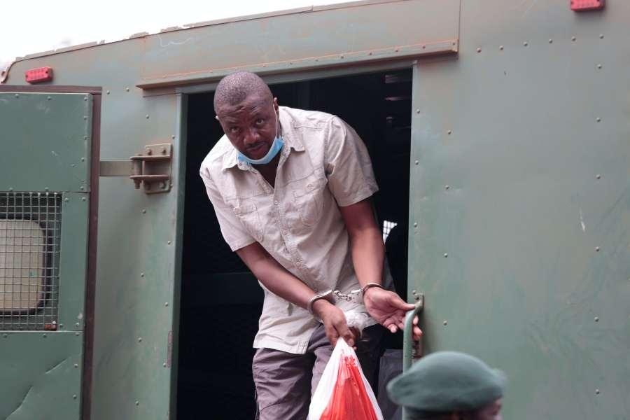 Hombre esposado con mascarilla se baja del camión de la prisión.
