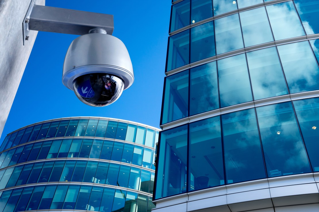 A CCTV camera in a city centre surrounded by high-rise offices