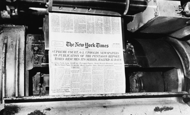 A printing press spits out of a copy of a newspaper.
