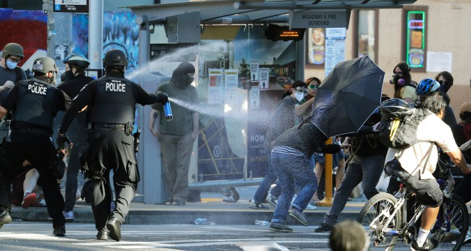 Police in protective gear spray chemical agents at demonstrators