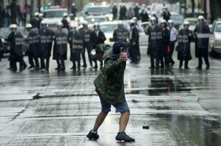 A protester throws debris at Cincinnati police officers in riot gear in 2001.