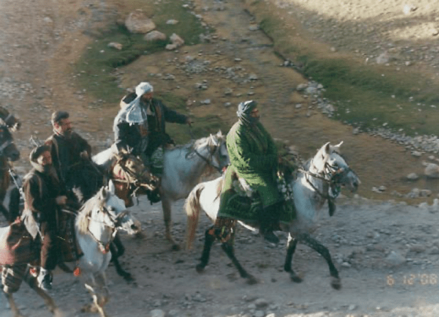 Armed men ride horses through rocky ground