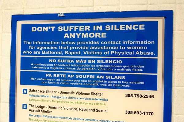 A sign on a wall that provides contact information to help victims of battering, rape and other physical abuse. domestic violence
