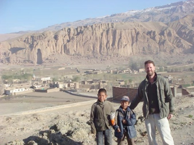 A man and two boys stand in front of cliffs showing a large void where a Buddha statue used to be