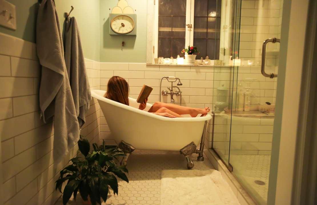Woman reads in home bathtub.