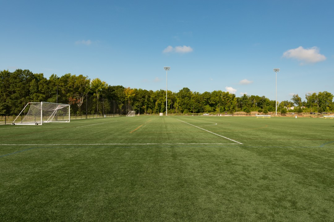 A neatly mown football field in a public park.