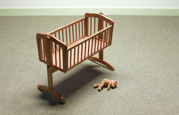 Empty crib with a stuffed animal lying beside it.