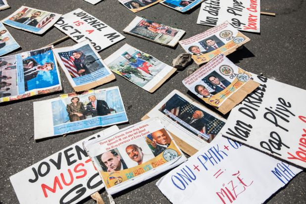 Protests signs seen laying on the ground, saying 'Jovenel must go' in English and Creole