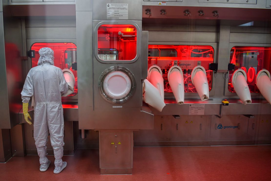 An employee in full protective gear works on assembling vaccine doses.
