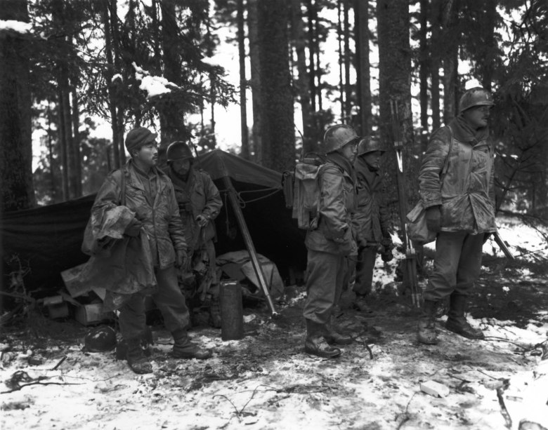 Japanese American soldiers stand in a French forest