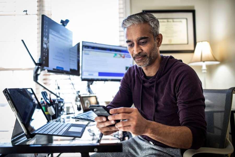 Un hombre en un escritorio con varias pantallas de computadora y mirando su teléfono celular.