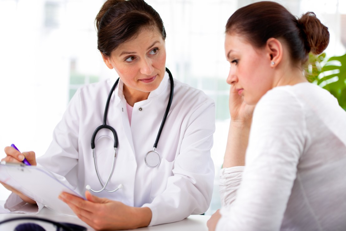Female doctor discusses test results with female patient.