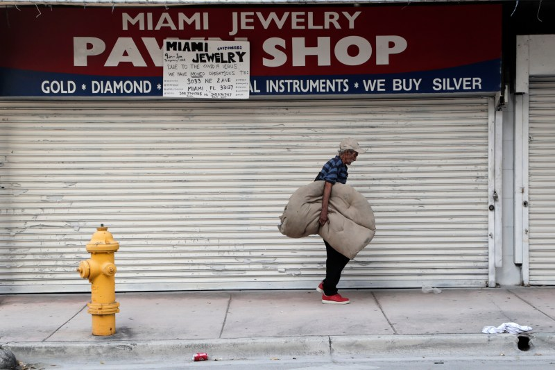 an older man holding a large cloth bundle under his arm walks along the sidewalk in front of the metal grate of a closed pawn shop