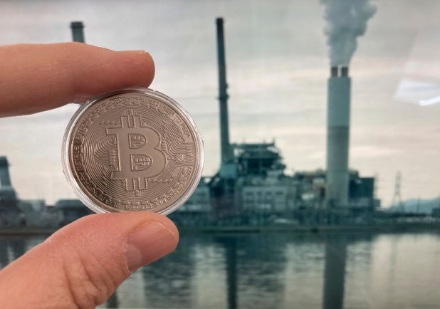 fingers hold bitcoin in front of smokestacks