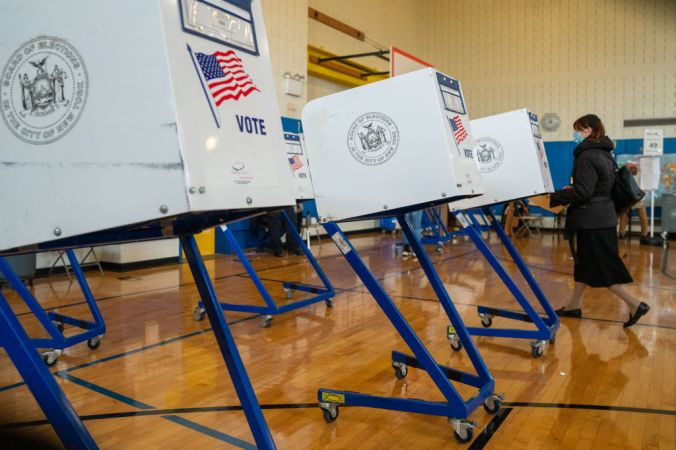 One voter standing at a white voting both that sits on blue metal legs with casters.