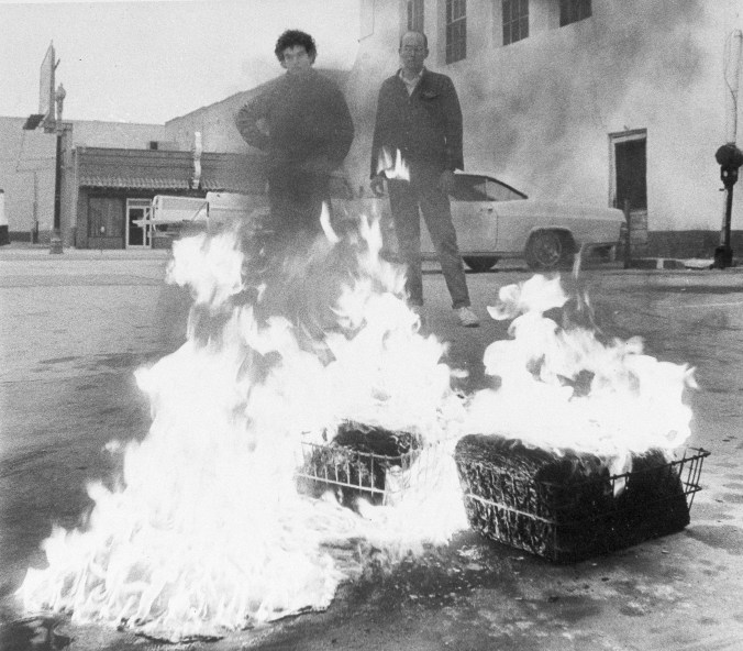 Two men stand in front of burning boxes