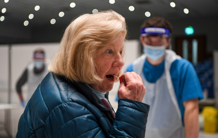 A woman inserting a swab into her mouth.