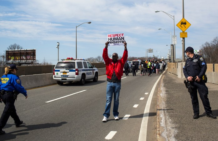 A man holding up a sign 'RESPECT HUMAN RIGHTS' as two police officers stand near him and approaching marchers.