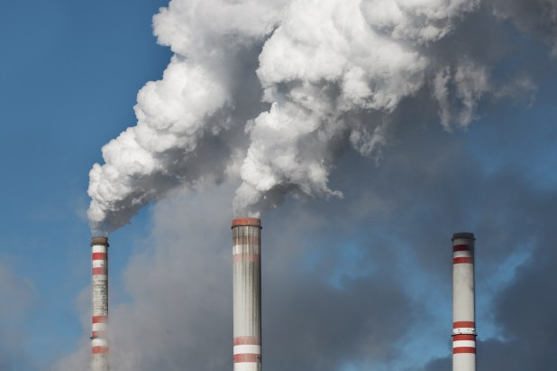Three smoke stacks belching white smoke from a coal-fired power plant.