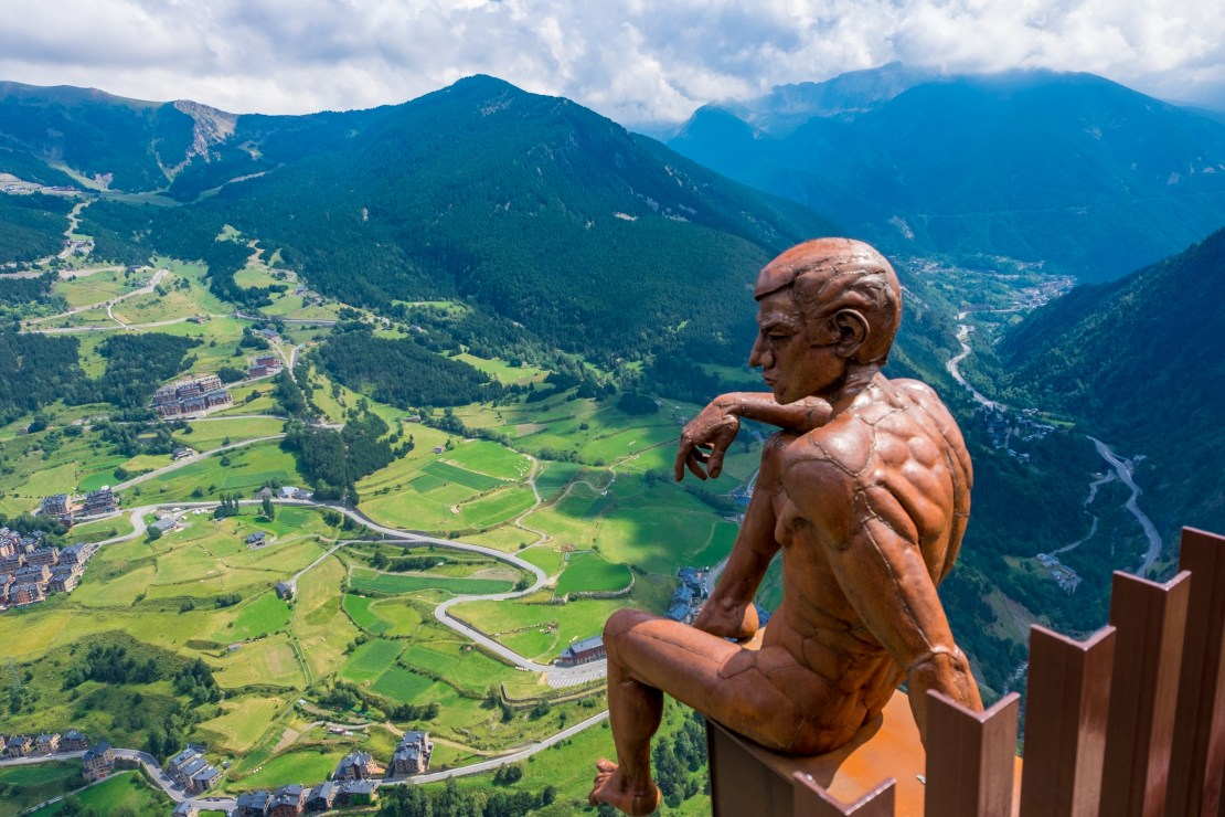 Statue looking over large mountain meadow and valley