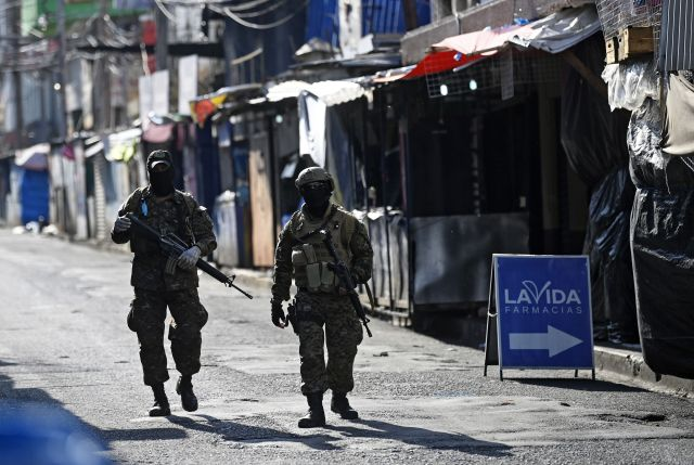 Two armed soldiers in full fatigues and face masks walk down a street lined with vendors