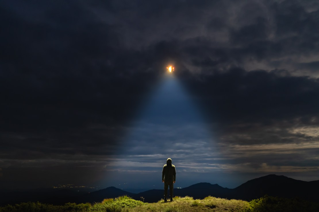 Artist's concept of a UFO shining on a male standing on the mountain