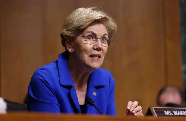 Elizabeth Warren sits at a Senate committee table as she speaks