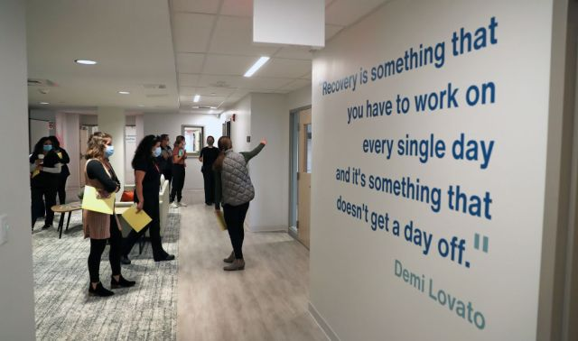 A tour group passes by a quote from Demi Lovato that's affixed to a wall at a drug recovery center.
