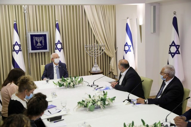 A group of people sit at a large table with white tablecloth and Israeli flags in the background.