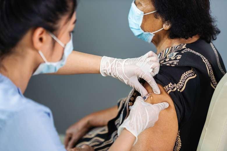 Médica aplicando a una anciana india una vacuna en el hombro