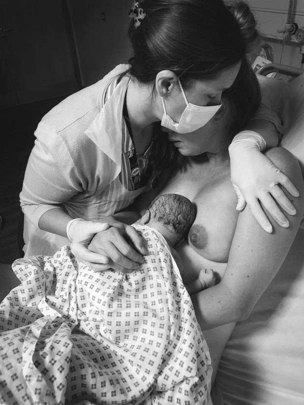 Midwife reassuring woman holding a newborn baby in hospital