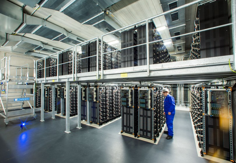 An engineer inspects stacked rows of power storage units.