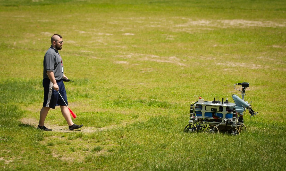 A person walks behind an autonomous robot