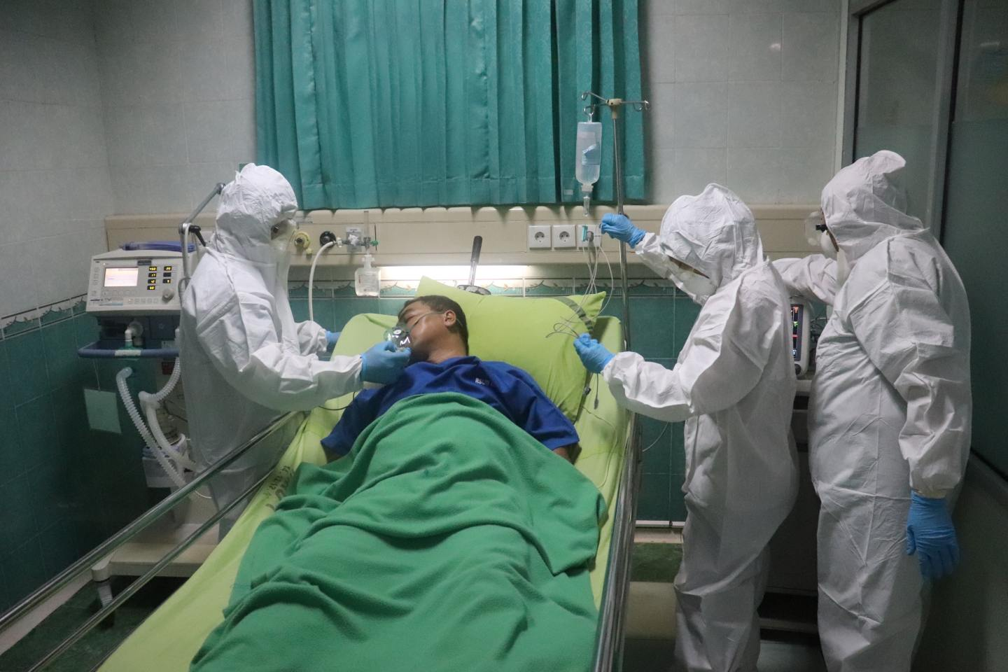 Man lies in green bed surrounded by three people in white protective suits.