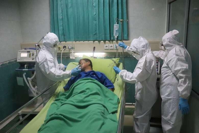 Un hombre yace en una cama rodeado de personas con equipos de protección.