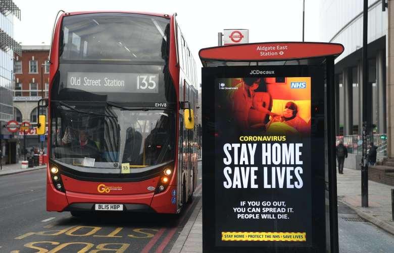 Un anuncio en una parada de autobús que dice: 'Quédate en casa, salva vidas'