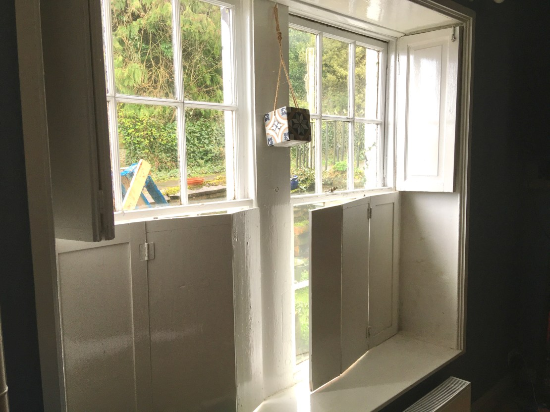 A white wooden window frame with attached shutters on the inside.