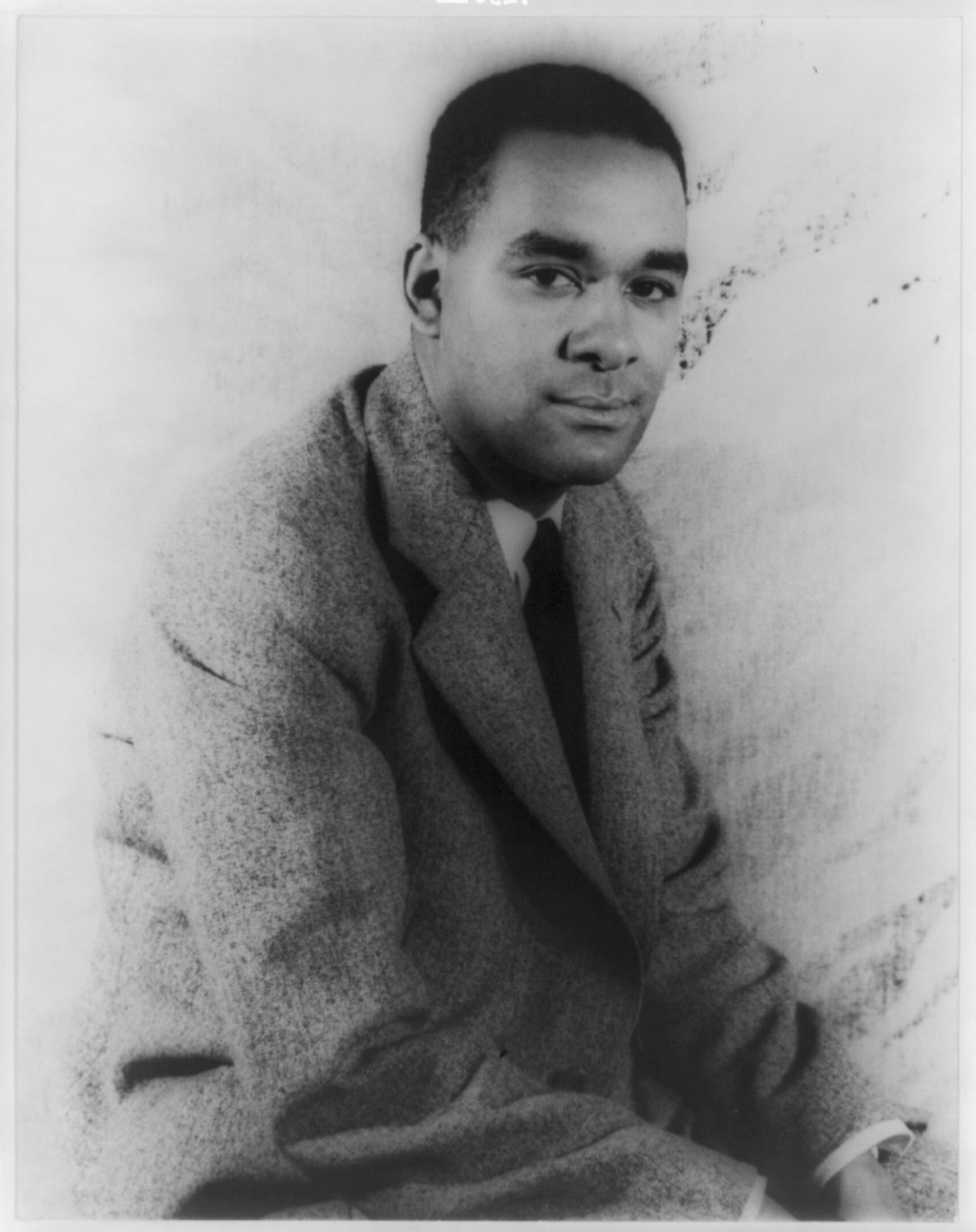 A black and white portrait of author Richard Wright, pictured seated.
