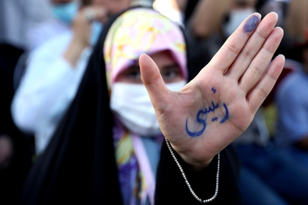 An Iranian woman holds out her hand, which has the name 'Raisi' on it written in Persian script