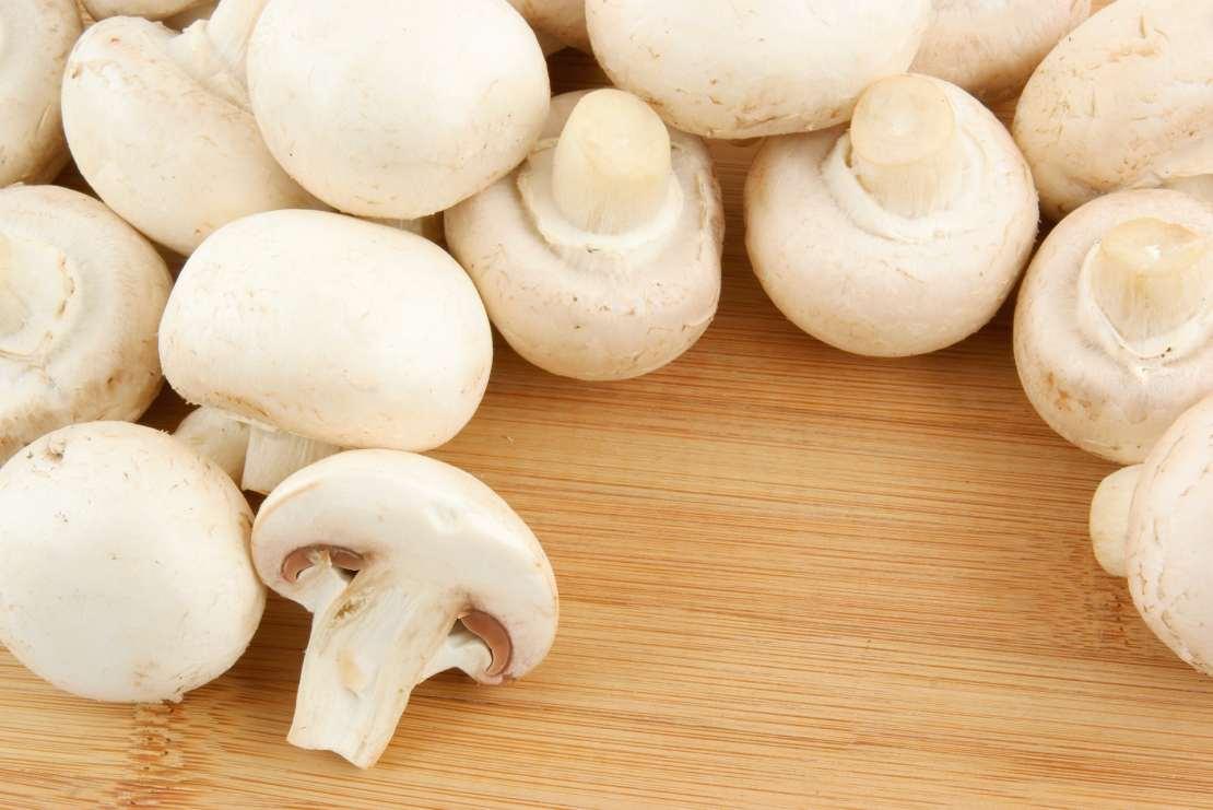 White mushrooms on wooden background.