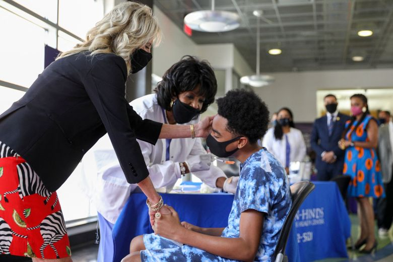 U.S. First Lady Jill Biden gives comfort to a patient at a vaccination clinic