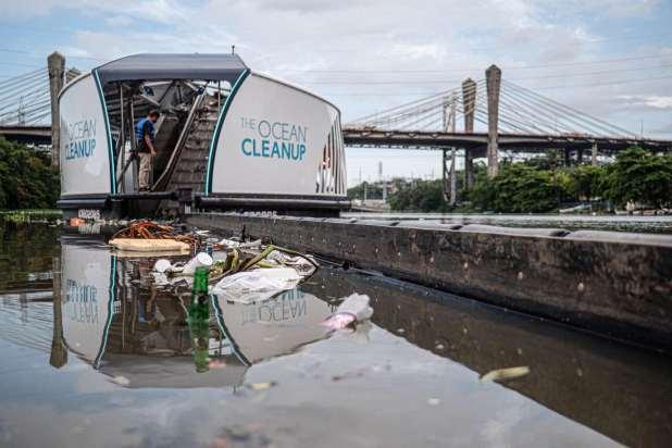 Large barge with conveyor belt pulling plastic debris out of river.