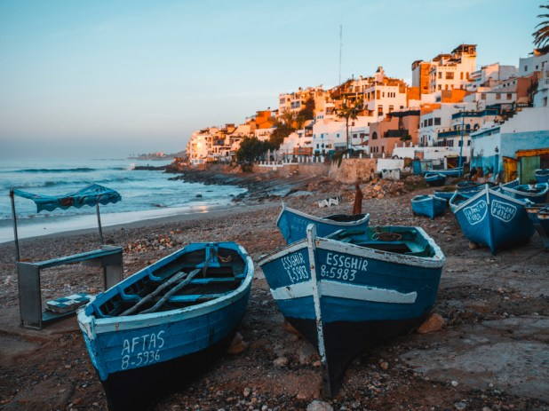 Traditional fishing boats line a beach in a coastal village of Morocco.