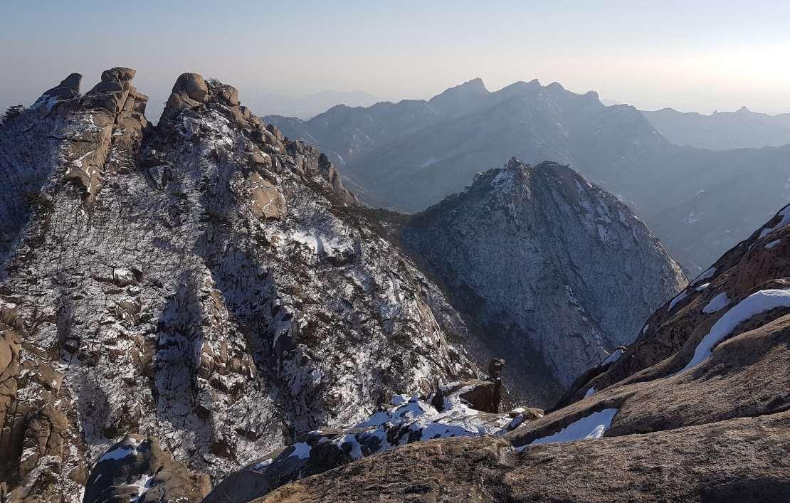 A rocky mountain vista with streaks of snow.