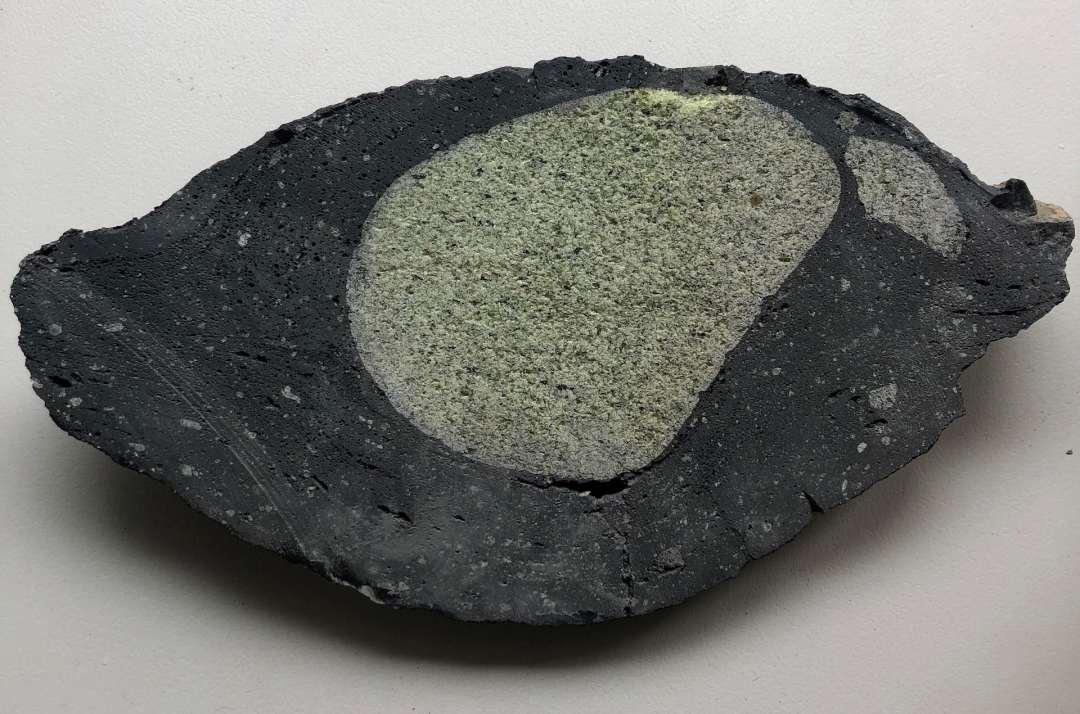 Green rock blob encased in black rock