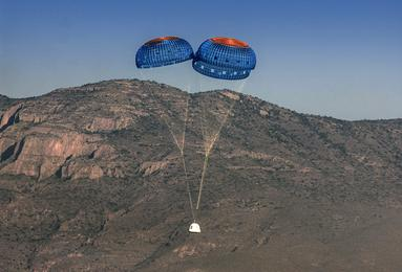 Image of Blue Origin's New Shepherd spacecraft landing with parachutes.