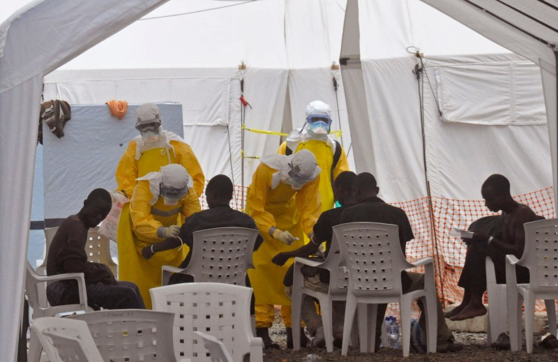 Health care workers in yellow protective equipment treating a group of people in a white tent.