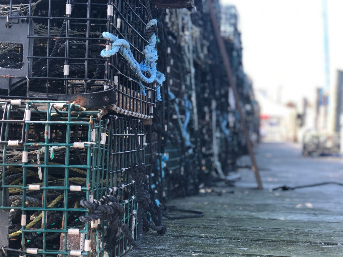 A row of stacked lobster pots on a harbour.