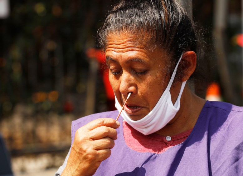 woman with lowered mask swabs her own nose