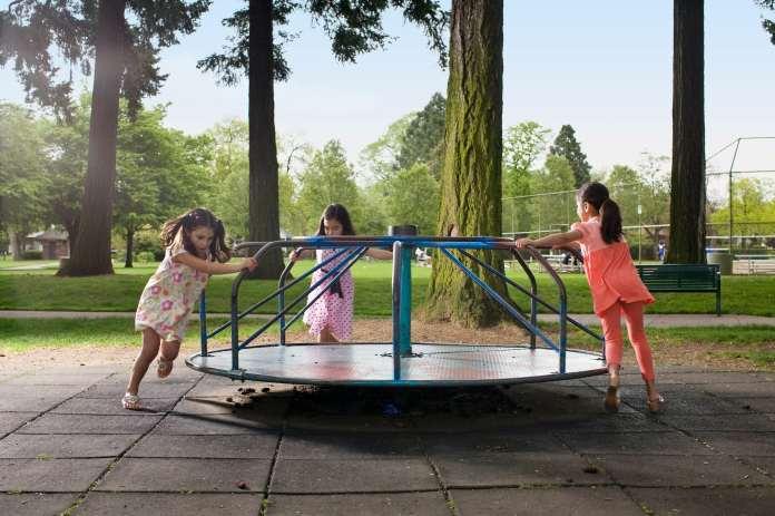 three girls playing on the playground carousel